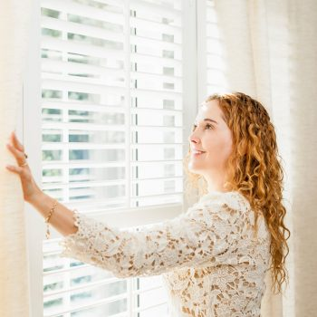 woman next to window blinds