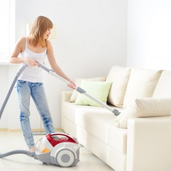 woman vacuuming sofa