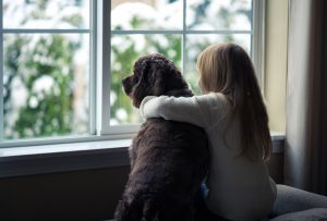 child with dog looking out window